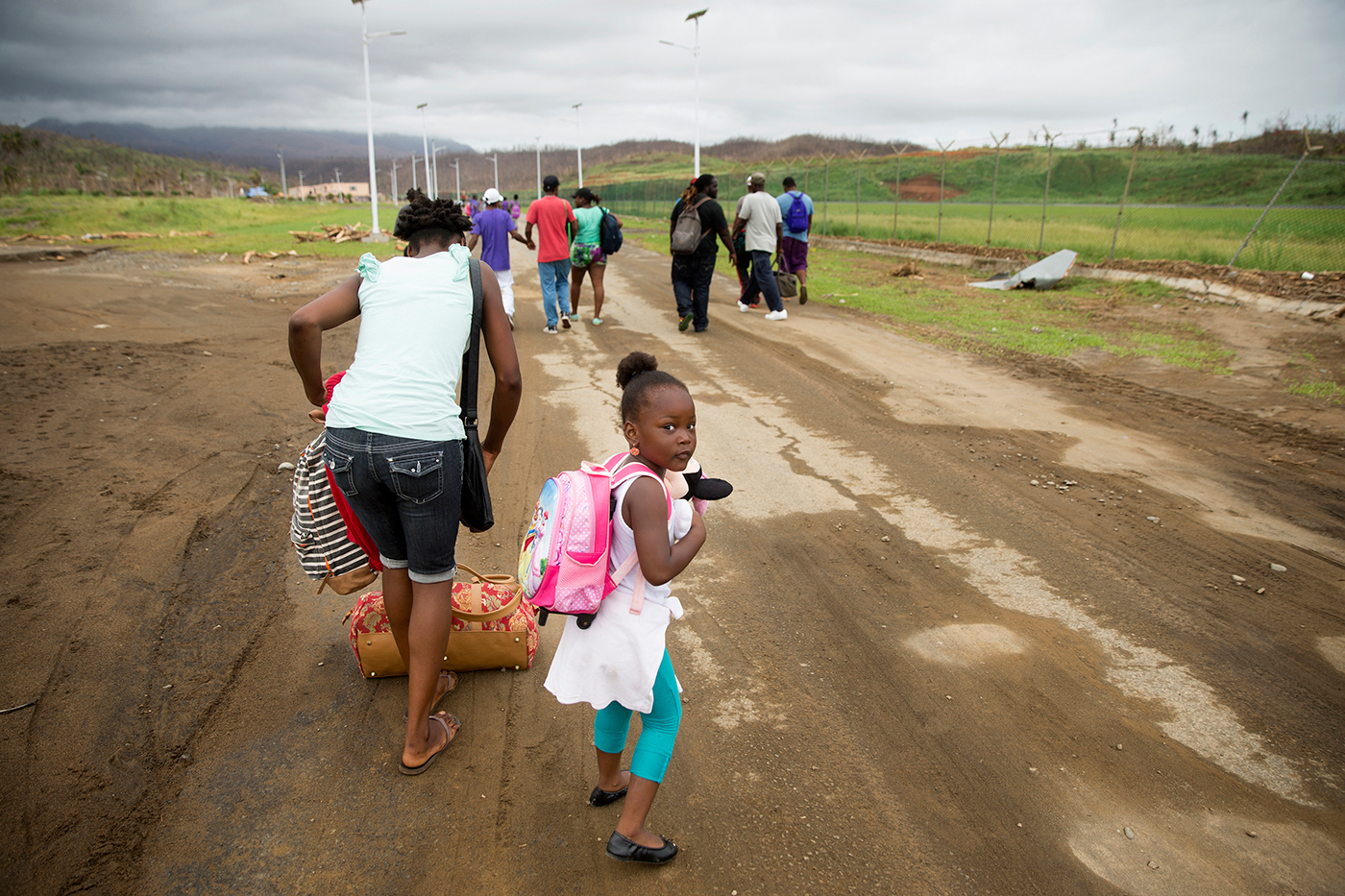 People walk towards Dominica's Douglas Charles Airport to try to get flights to Antigua ten days after the hurricane hit