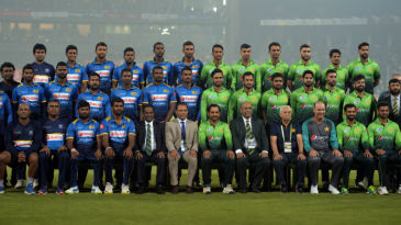Players pose against the backdrop of packed stands in hazy Lahore
