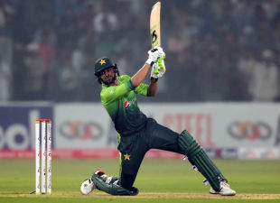 Shoaib Malik is down on one knee as he carves a full-length delivery over cover