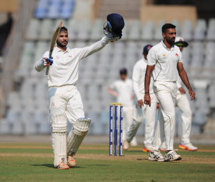 Aditya Waghmode raises his bat after reaching a hundred