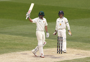 Alex Doolan raises his bat after notching up his double-hundred