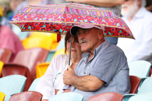 Fans wait in anticipation for play to resume after a protracted rain break