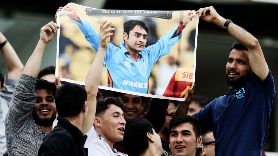 Fans hold up a poster of Rashid Khan
