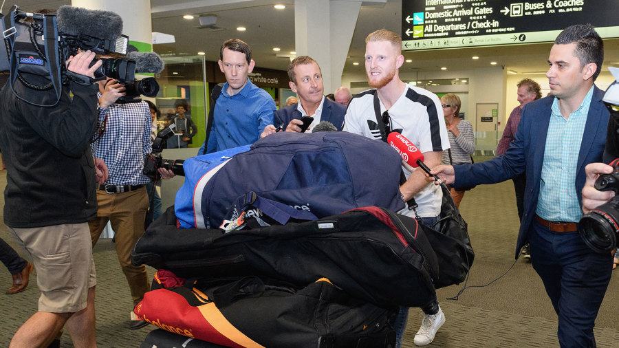 Ben Stokes walks through the airport surrounded by media