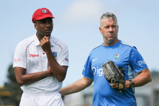 Miguel Cummins and West Indies coach Stuart Law look on after having a chat in between overs