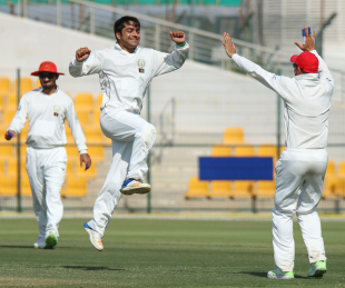 Rashid Khan leaps in the air to celebrate a five-wicket haul