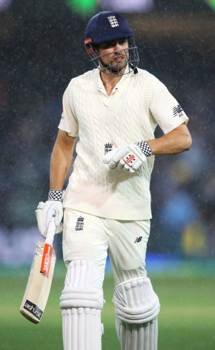 Alastair Cook heads off as the rain falls