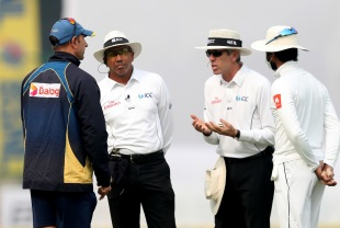 Sri Lanka coach Nic Pothas and captain Dinesh Chandimal have a chat with the umpires as bad weather stops play