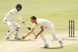 Josh Hazlewood stoops to claim a low catch off Alastair Cook