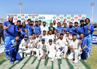 Sui Northern players and staff pose with the Quaid-e-Azam Trophy