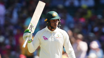 Usman Khawaja raises his bat on reaching fifty