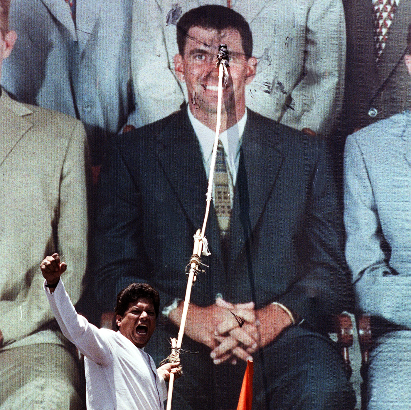 A man applies paint to a billboard image of Hansie Cronje as a sign of protest