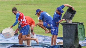 Bernard Scholtz empties water off the covers as JJ Smit crouches in frustration over the falling rain