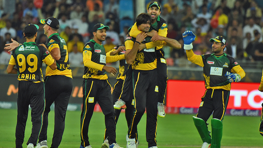 Mohammad Irfan is mobbed by his team-mates upon picking up a wicket