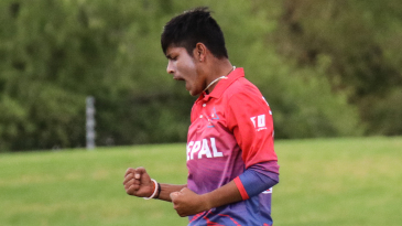 Sandeep Lamichhane pumps his fists after taking a wicket
