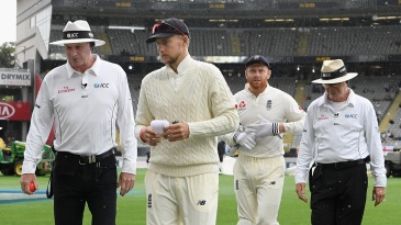 Joe Root walks off the field as rain sets in