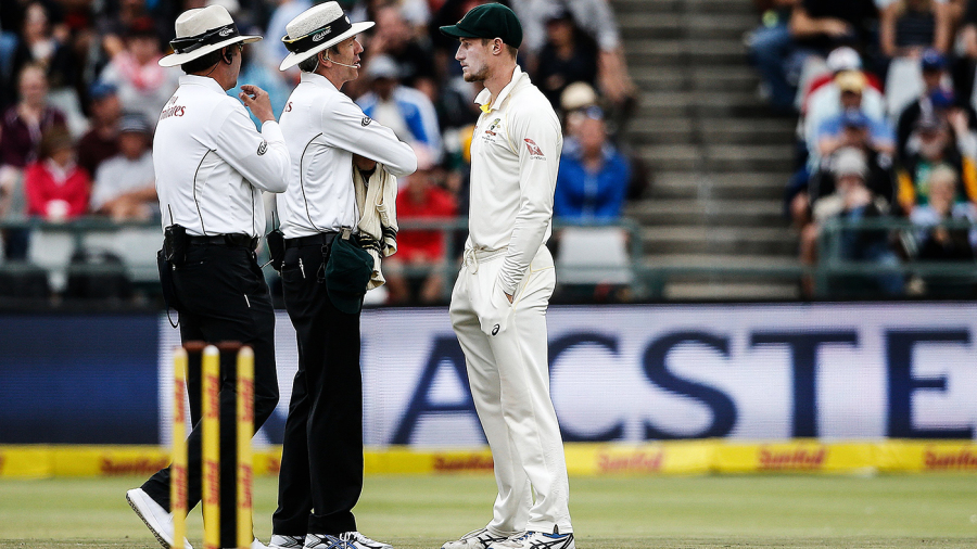 The umpires have a chat with Cameron Bancroft about working on the ball