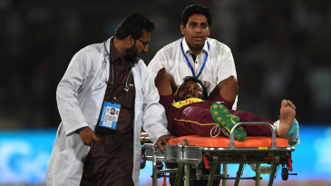 Veerasammy Permaul gestures as he lies on a stretcher after being injured