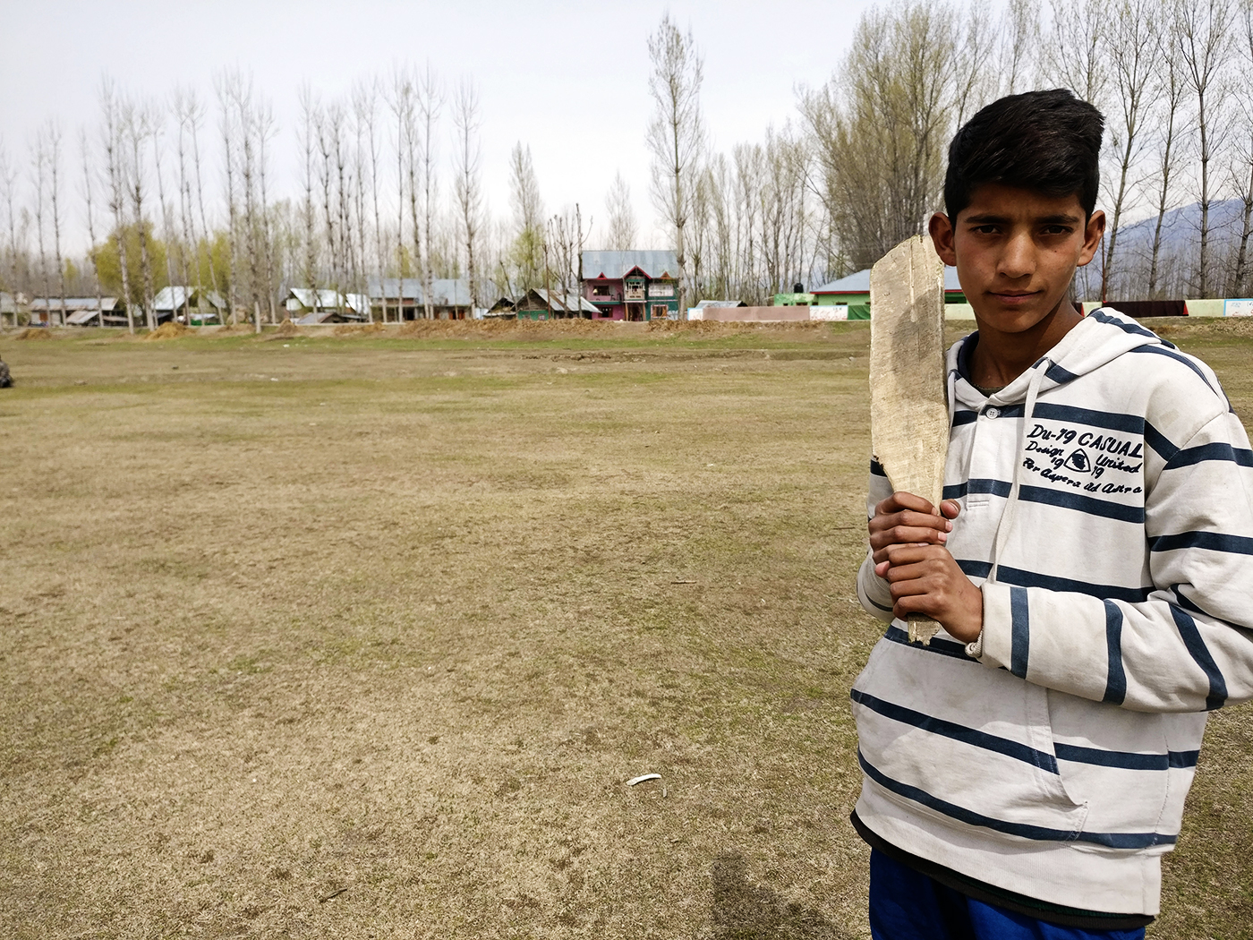 Manzoor's youngest brother, pictured holding a typical handmade bat from Sumbal