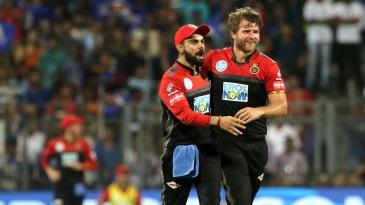 Virat Kohli and Corey Anderson celebrate a wicket