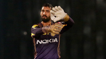 Dinesh Karthik adjusts the field