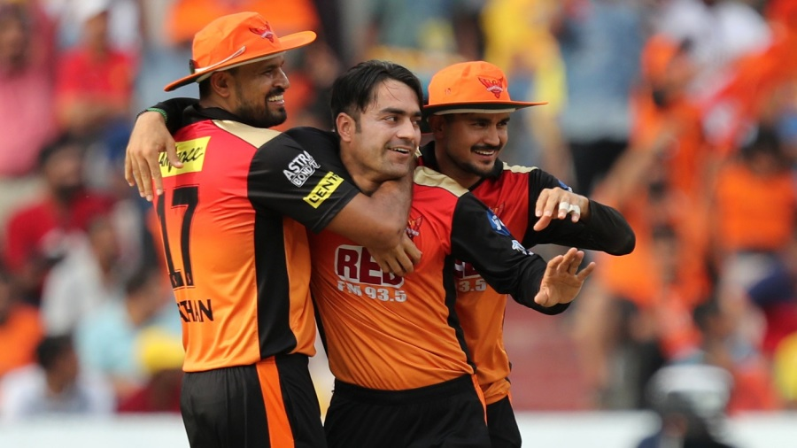 Rashid Khan is mobbed by team-mates after taking a wicket