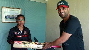 Tamim Iqbal hands over a bat to Rumana Ahmed