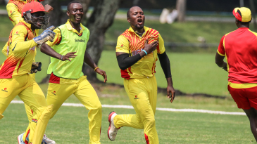Uganda captain Roger Mukasa sprints off after taking the final wicket to secure victory