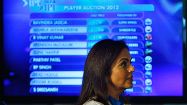 Mumbai Indians owner Nita Ambani walks past a screen displaying the players up for the IPL auction