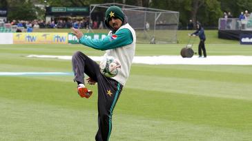 Saad Ali kicks a football around with his team-mates during a rain delay