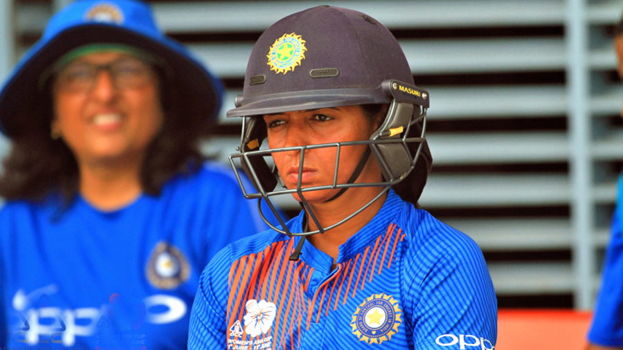 A pensive Harmanpreet Kaur awaits her turn in the dugout