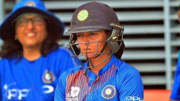 A pensive Harmanpreet Kaur awaits her turn in the dugout