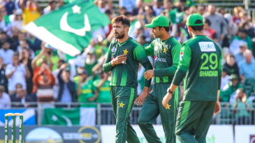 Mohammad Amir winces and tugs at his left shoulder after taking a wicket