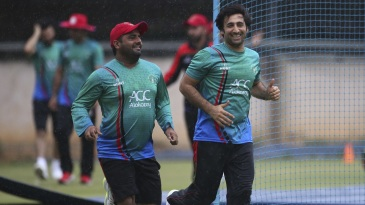 Mohammad Shahzad and Asghar Stanikzai run for shelter as the rains come down on match eve