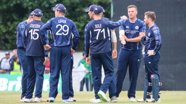 Scotland celebrates after Mark Watt's first wicket of the match