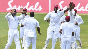 Jason Holder and the West Indies players celebrate a wicket
