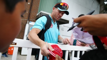 David Warner signs a cap for a fan