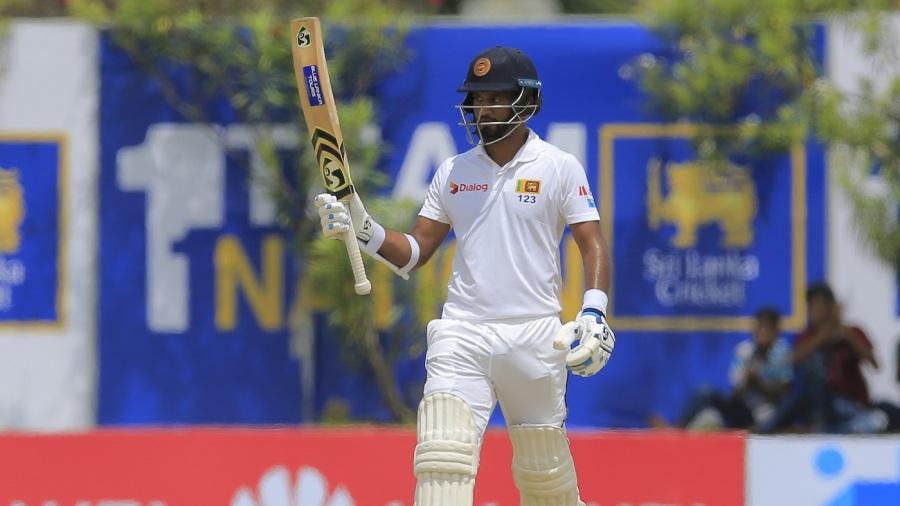 Dimuth Karunaratne raises his bat after reaching a half-century