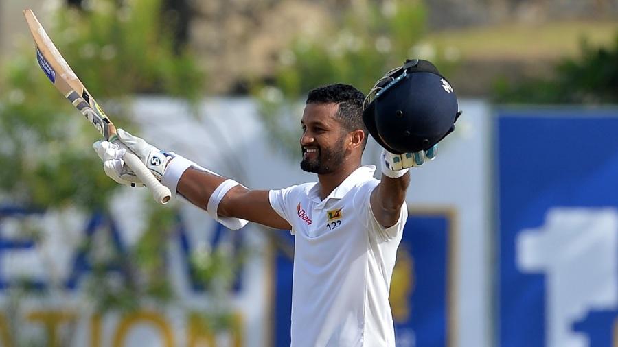 Dimuth Karunaratne raises his bat after reaching a century