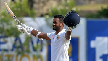 Dimuth Karunaratne raises his bat after reaching a century