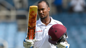 Kraigg Brathwaite raises his bat after getting to his century