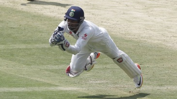 Wriddhiman Saha dives to take a catch
