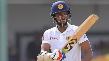 Danushka Gunathilaka raises his bat after bringing up a fifty