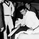 Muhammad Ali examines a cricket boot in the West Indies dressing room at Lord's, England v West Indies, Lord's, 1st day, June 16, 1966