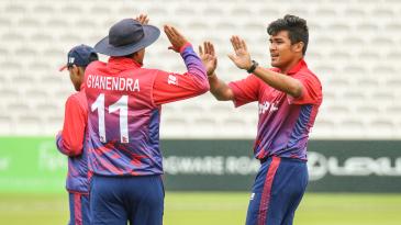 Gyanendra Malla high fives Karan KC for taking a wicket