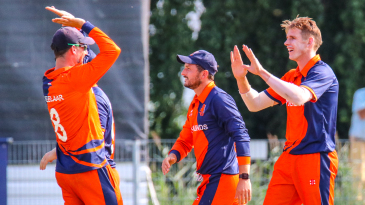 Fred Klaassen gets high-fived by captain Pieter Seelaar after taking a key wicket