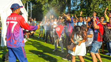 Paras Khadka gives the traveling Nepal fans a champagne shower to celebrate a famous win