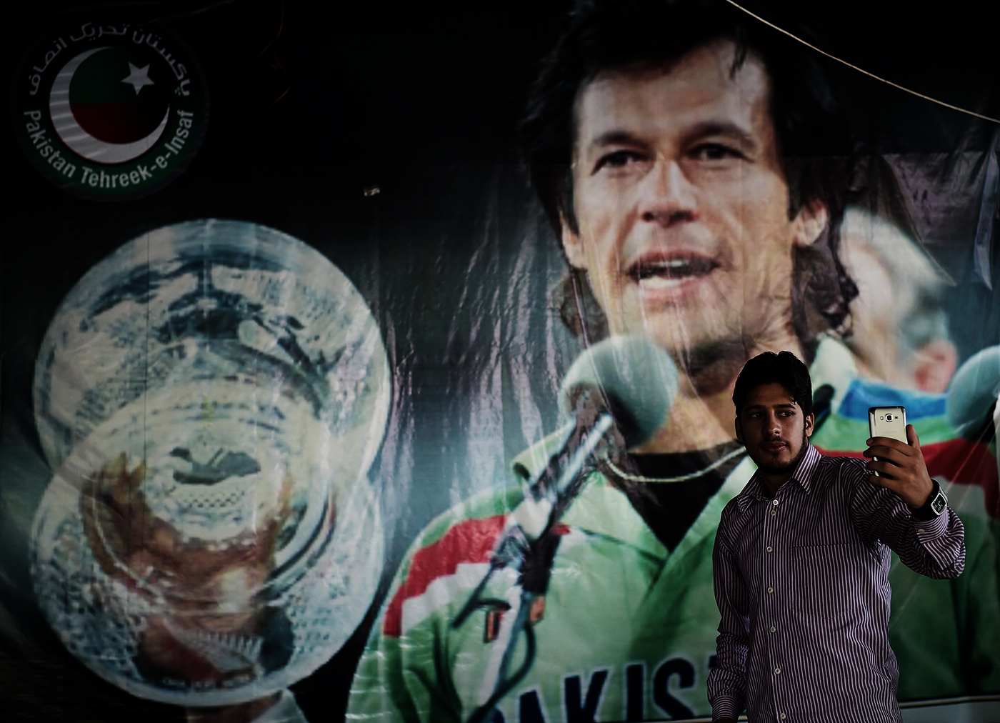A man take a photo with a poster of Imran Khan in the background