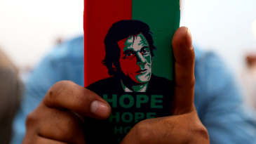 A person looks at a mobile phone with Imran Khan on the back cover