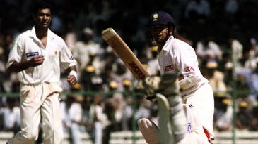 Waqar Younis watches as wicketkeeper Moin Khan fails to stop a shot from Sachin Tendulkar